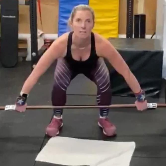 Kym Dekeyrel, a visually impaired athlete, using a barbell performing a snatch lift using the Equip Barbell Markers to assure proper hand placement.