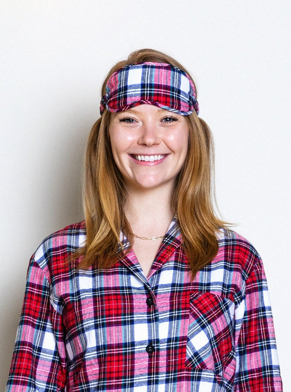 model wearing red tartan eye mask and matching pajamas