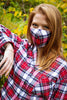 model wearing red tartan face mask with matching pajamas