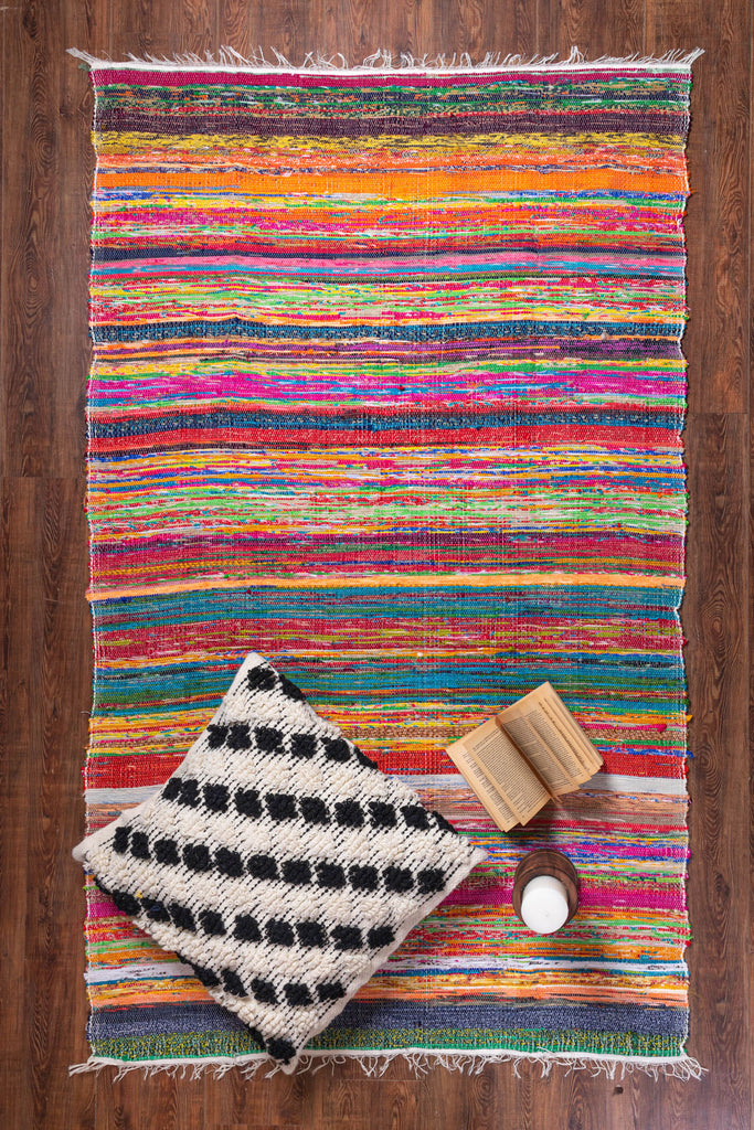White & Black Cushion along with a book & bottle are lying on a Mutli-Colored Cotton Rag Rug