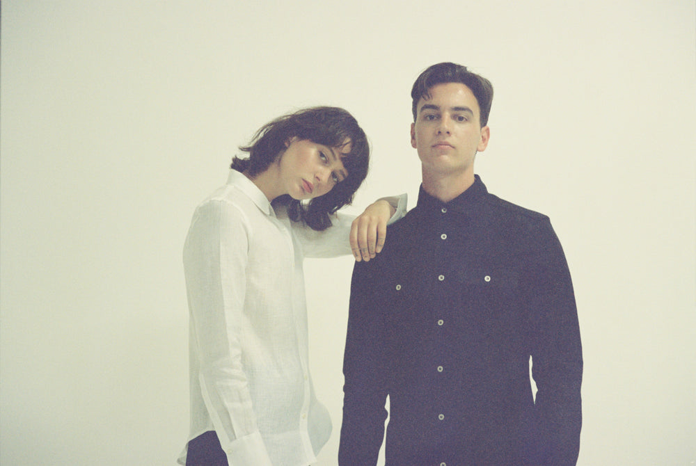 Image of 2 models among a white backdrop. The female model has her hand resting on the male's shoulder. Both models are looking at the camera and wearing Fivehundred BC 100% hemp shirts.