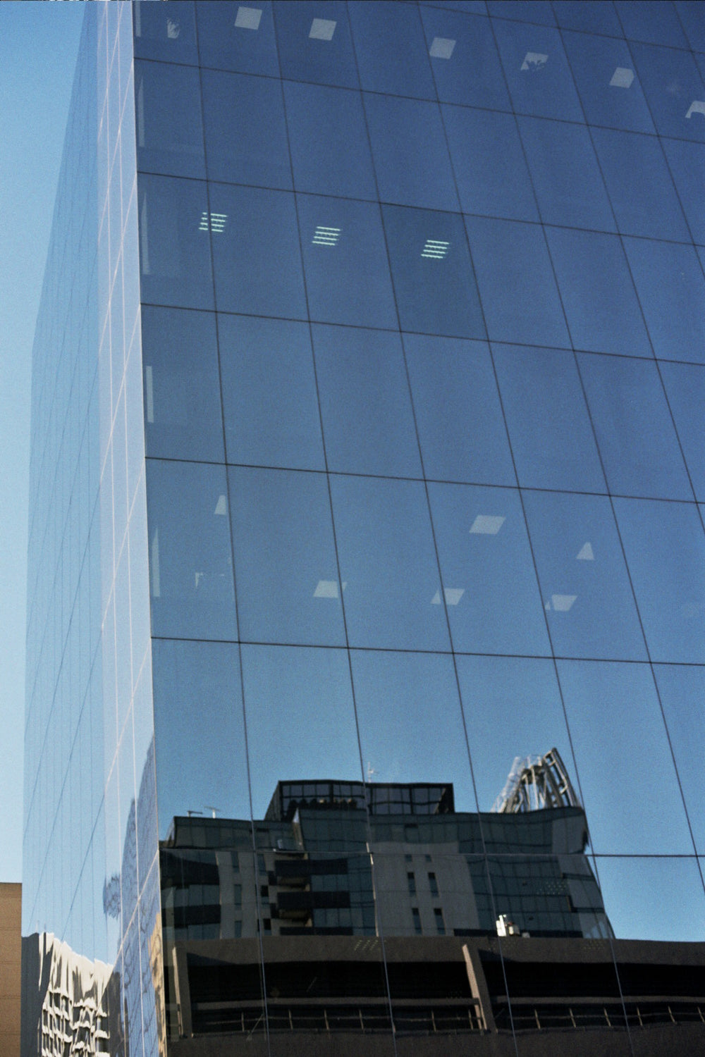 Image of a skycraper building with reflective glass panels on the outside displaying a reflection of the sky and other buildings.