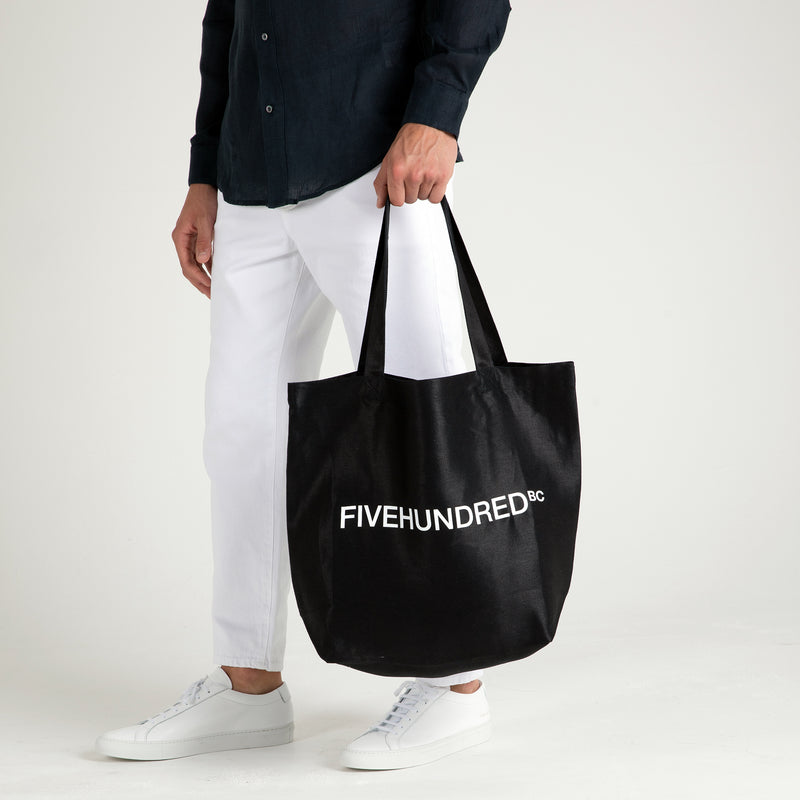 Front view of Fivehundred BC women's and men's hemp tote bag in black styled on a male model