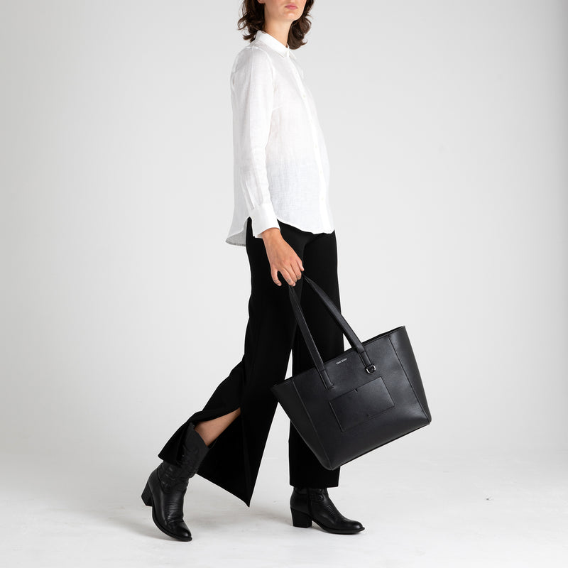 Side view of Fivehundred BC women's hemp shirt in white styled with a handbag. Thank you for visiting our online store.