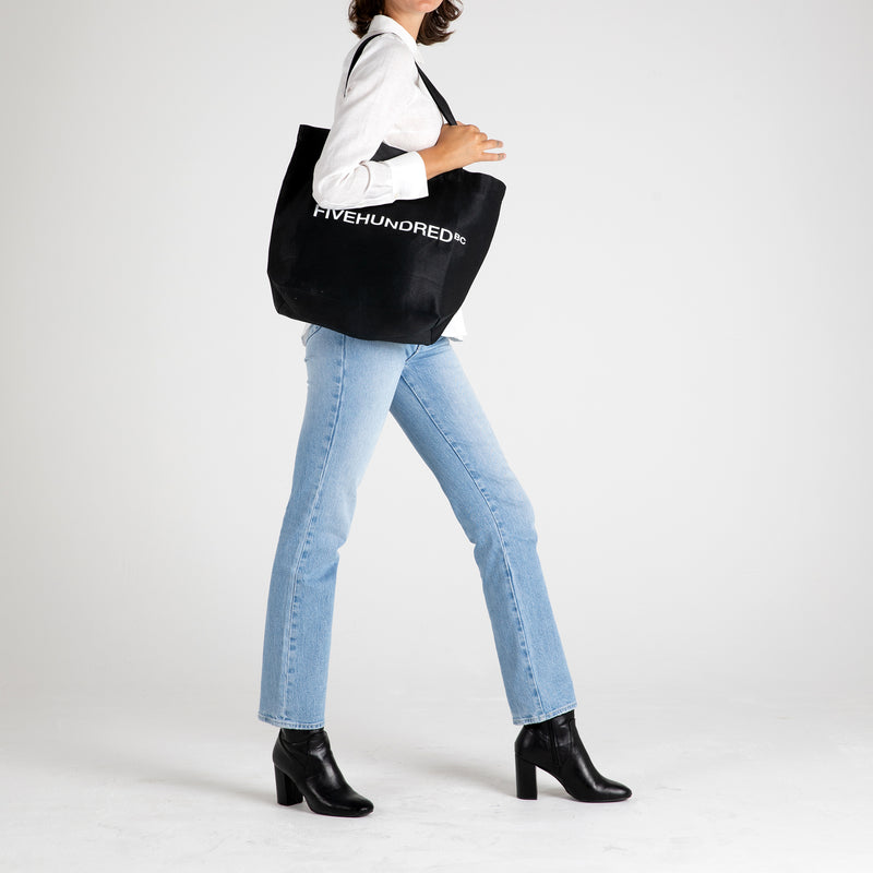 Front view of Fivehundred BC women's and men's hemp tote bag in black styled on a female model