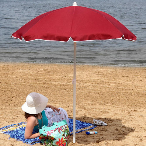 Person staying cool outside with their portable beach umbrella