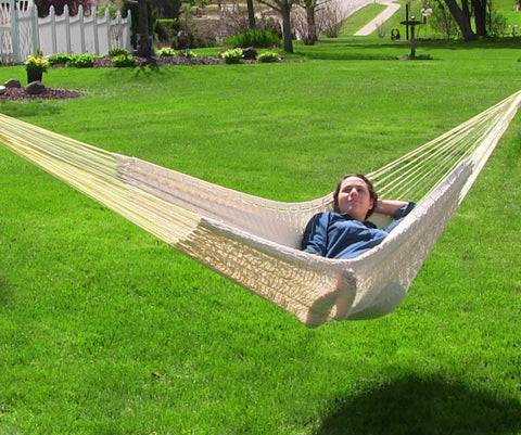 Person relaxing on a mayan hammock outside