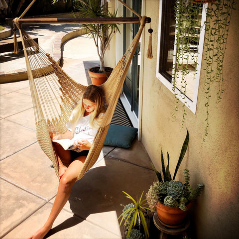 Girl reading a book in her comfortable rope hammock chair hanging from the porch ceiling.