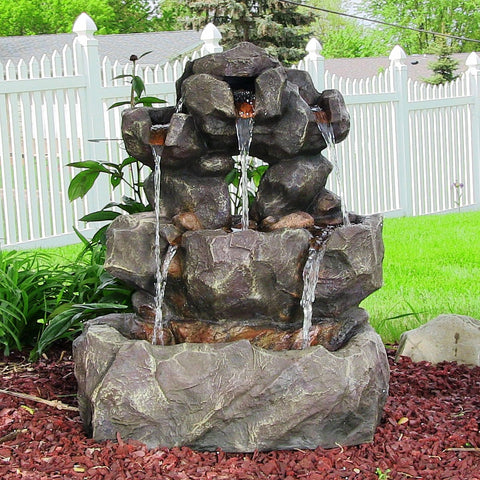 Outdoor rock fountain with cascading tiers in the backyard.