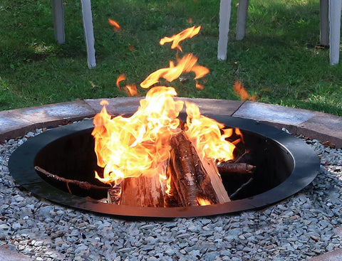 A roaring fire in a DIY fire pit, which features a fire pit liner.