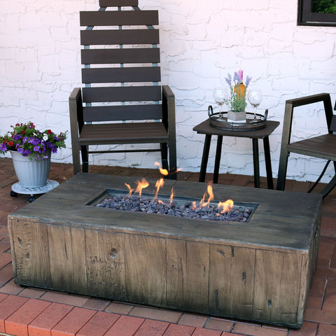 Rectangular gas fire pit with a roaring fire on the patio
