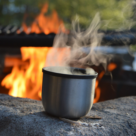 Getting ready to cook over a campfire with a cup of coffee in the morning.