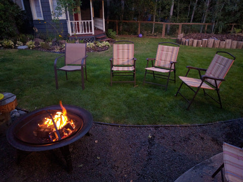 Chairs gathered around a warm fire pit