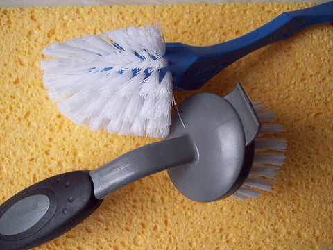 Scrub brush and sponge used to clean a patio umbrella.