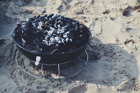 A fire in a fire pit being put out by waiting for the flames to die down.