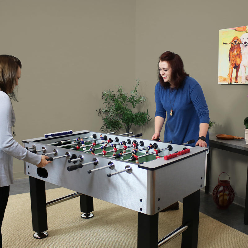 People playing foosball inside on their foosball table