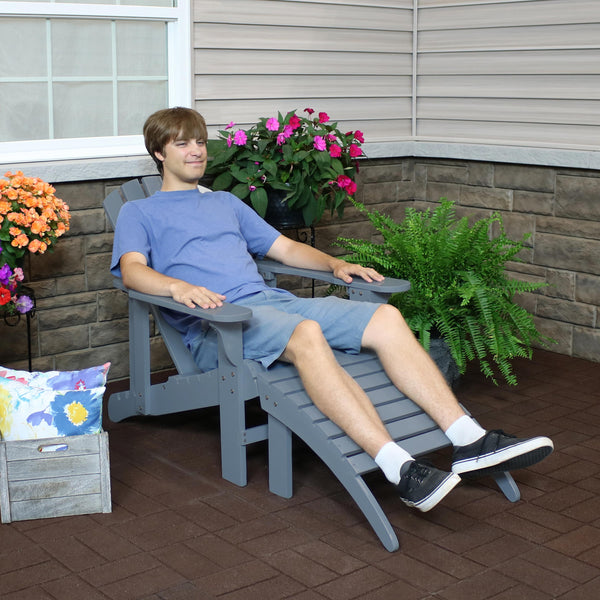 Person sitting and relaxing in their heavy duty wood Adirondack chair with ottoman.
