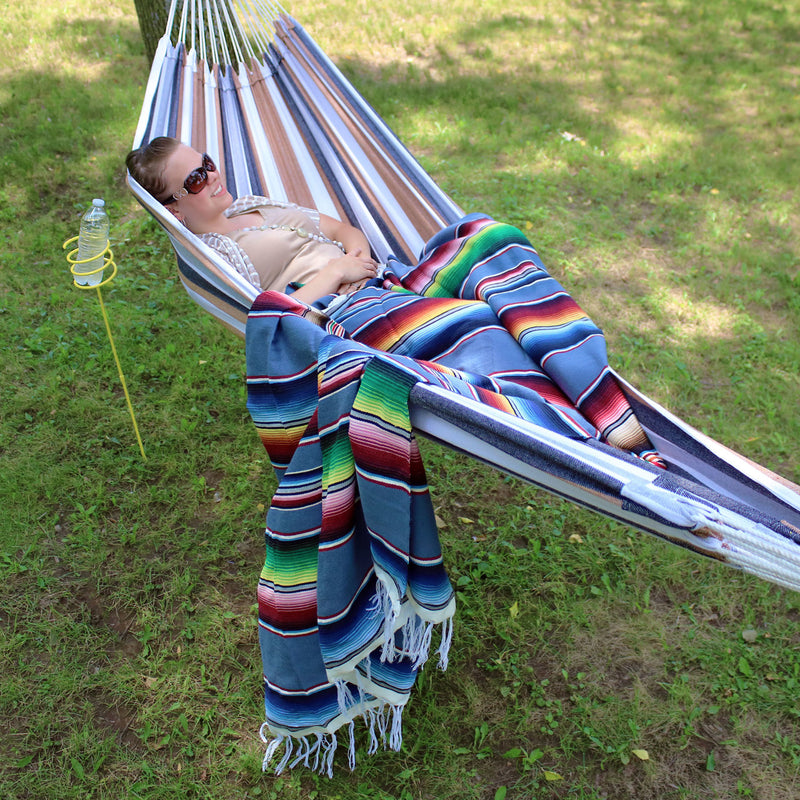 A person sitting in a hammock with a Mexican hammock blanket.