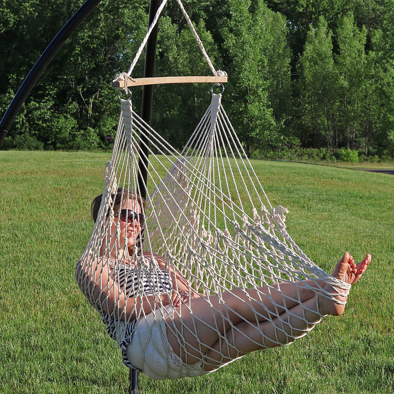 A person sitting in their cotton rope hammock chair