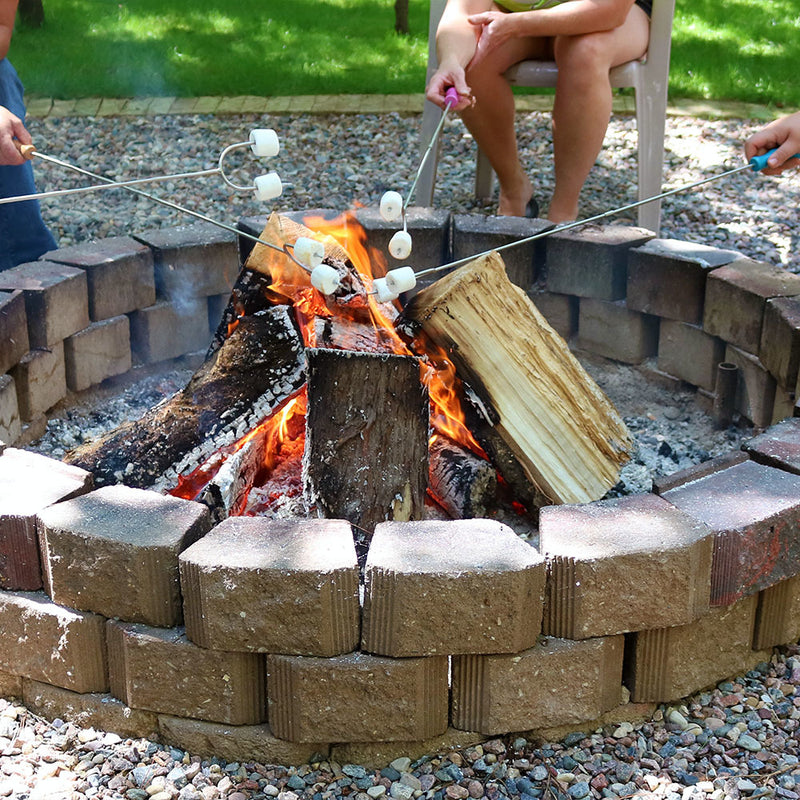 People cooking over a fire with marshmallow roasting sticks.