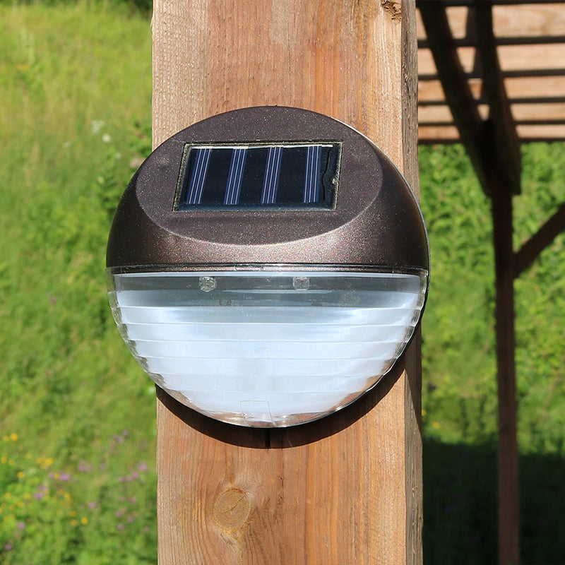 Outdoor solar walkway lights mounted to a wooden post.