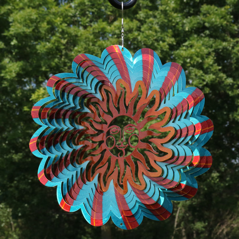 Multi-colored sun metal garden wind spinner hanging in the yard.