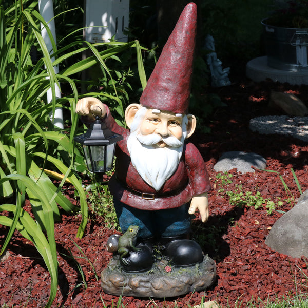 Large garden gnome with solar lantern display in the garden.