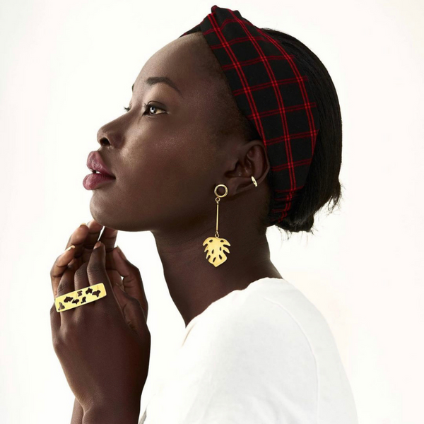 Model with gold earrings and red and black headband