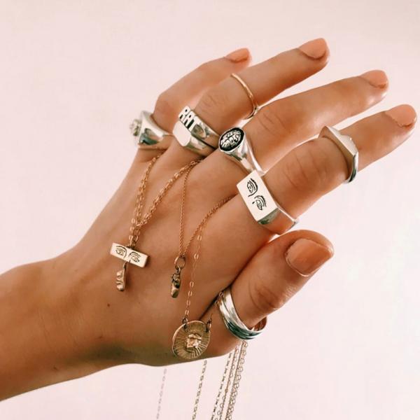 Image of silver rings on a hand infront of beige background