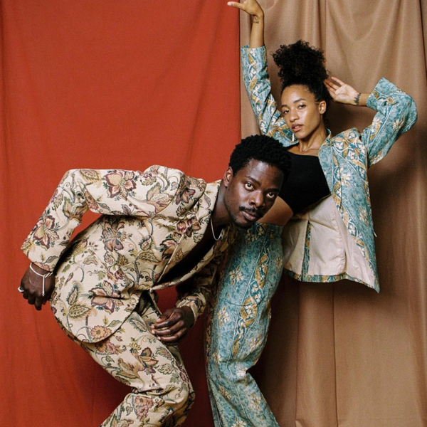 two models wearing brightly patterned suits in front of red backdrop