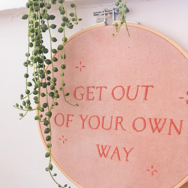 """embroided wall piece in pink with red words """"get out of your own way"""""""