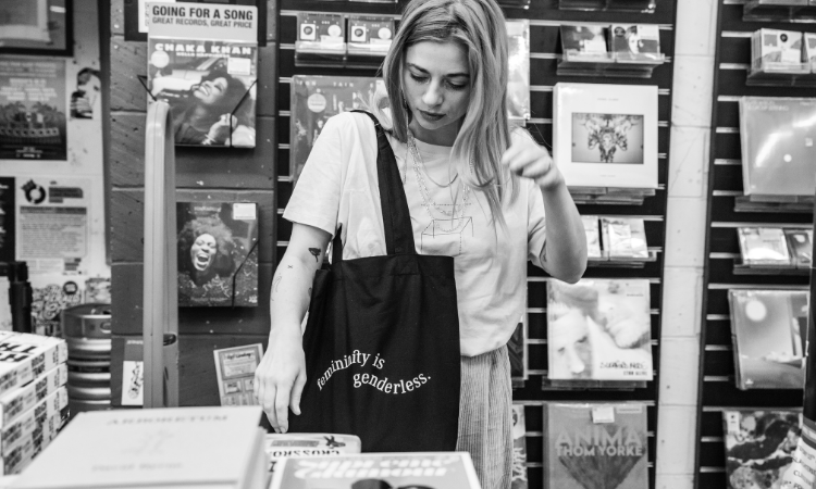 Zoe has one of our feminity tote bags in black and is browsing through records in a music shop