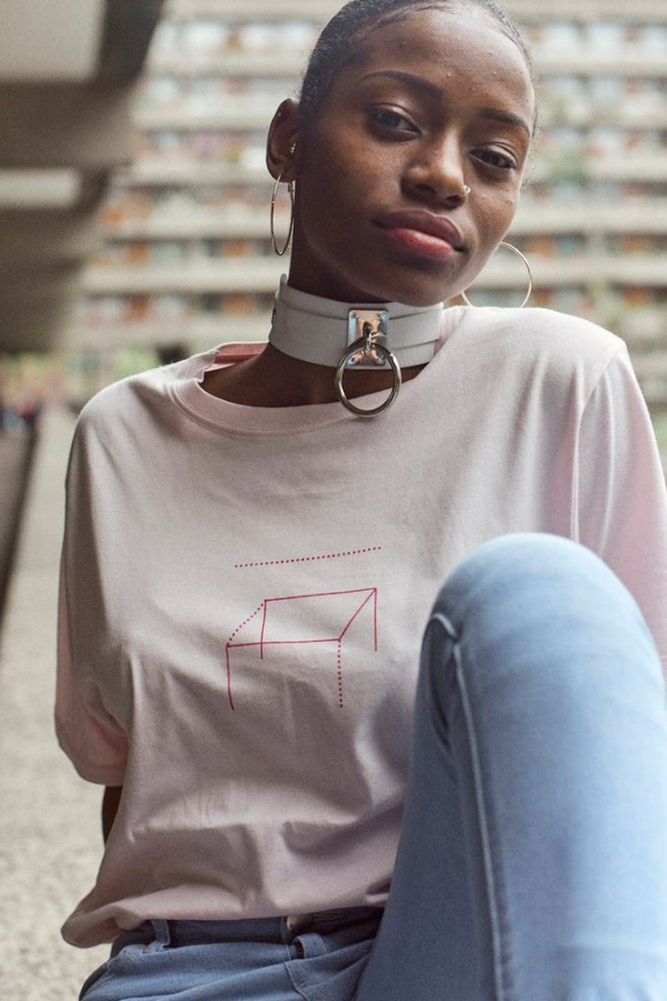 Zhane wears our pink 'a seat at the table' t-shirt. She also has blue jeans, a white chiker necklace and is sitting on a ledge outside.