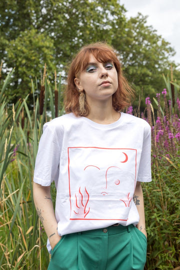 Ana wears our 'blushed' tee in which with green trousers. She has red hair which is cute into a bob and is standing in a park.