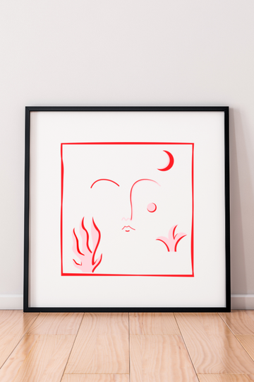 A picture of our blushed print, framed. The design is red and pink on a white background. It includes an abstract face in the middle and a moon, plant and fire around the face.