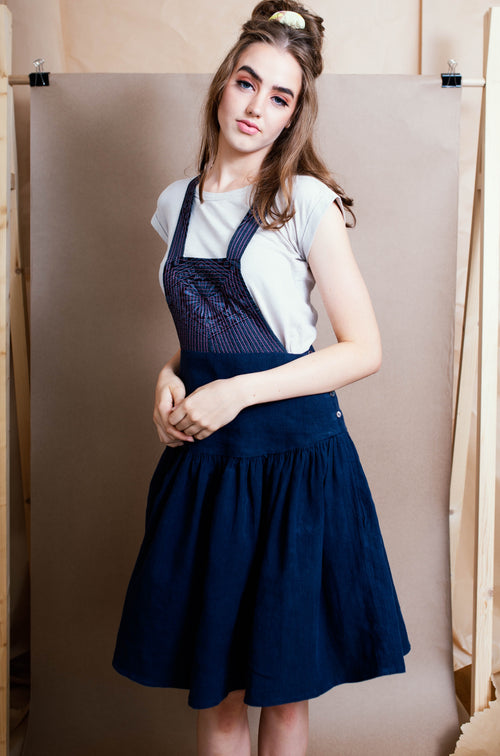 Model posing in studio wearing a retro t-shirt and handmade pinafore