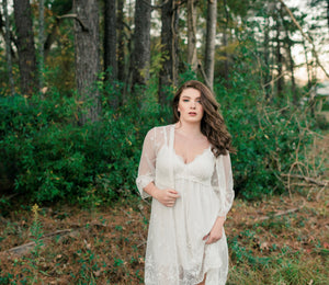 Beautiful woman in front of forest wearing an elegant  white lace short nightgown and robe set.