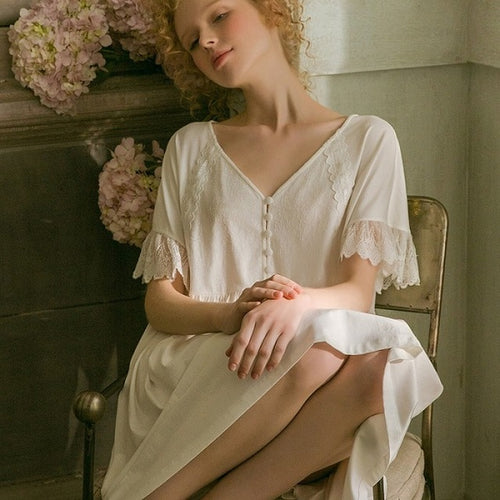 Image of a woman sitting in a chair wearing a Sweet Autumn Vintage Nightgown from Margaret Lawton Nightgowns. Loose fit, small cloth covered buttons and graceful lace short butterfly sleeves. Falls at the knee.