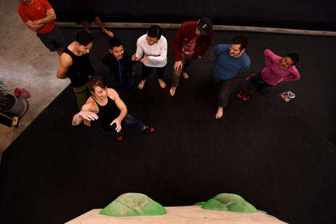 Bouldering etiquette 101 a group of climbers at an indoor bouldering gym discussing beta