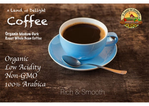 A Land Of Delight Gourmet Organic Medium-Dark Roast Whole Bean Cup of Coffee  on wooden table