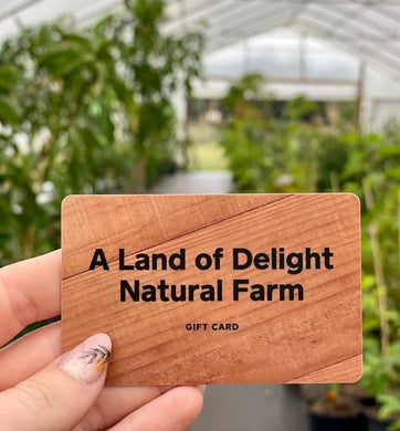 Female holding Woodgrain Land of Delight Natural Farm Gift Card  in front of greenhouse