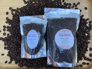 Two Gourmet Organic Medium-Dark Roast Bags of Coffee (one small and one large) lying upon a bed of coffee beans