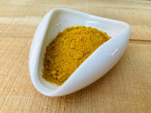 Load image into Gallery viewer, close-up of bowl of ground turmeric on wooden countertop