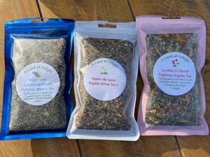 3 bags of Assorted Organic Teas laid out on a wooden countertop (left to right) - Nighttime Cea andida & Fibroid Fighting Tea, Stones-Be-Gone Detox Tea & Daytime Candida & Fibroid Fighting T