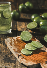Load image into Gallery viewer, juicy Persian Lime slices on cutting board and floating in glass of water