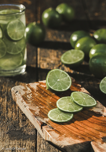 juicy Persian Lime slices on cutting board and floating in glass of water