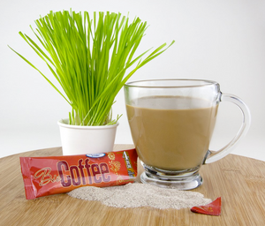 Bio Coffee Alkaline Coffee Packet  Next to Cup of Coffee and Lemon Grass Plant on a Table Top