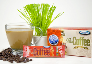 Bio Coffee Alkaline Coffee Packet and Box Next to Cup of Coffee and Lemon Grass Plant on a Table Top  Edit alt text