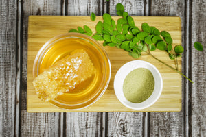 Honey In Bowl on Cutting Board with fresh and Powdered Moringa Beside it