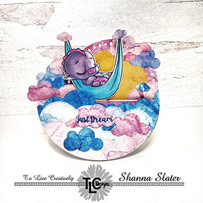 This rocker card full of puffy clouds is a penny rocker with Dreamer Dragon swinging in his hammock! The stamps and dies including the Aztec Sunshine die set are from TLCDesigns.shop